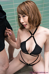 Squatting In Swimsuit Holding Flaccid Cock